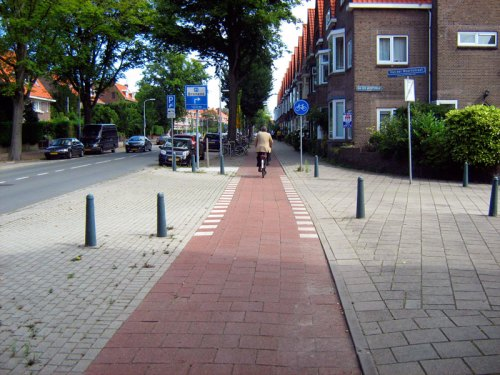 The view of a Dutch-style continuous-path minor junction from the view of a bike rider. The cyclepath and footpath both continue across the junction, and the minor road is disconnected from the main road. Cars have to mount the pavement and cross both paths to get between the two roads.