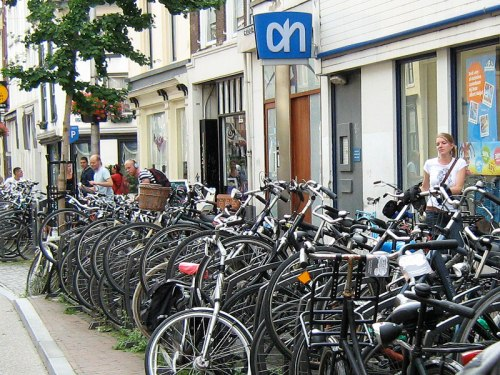 A huge number of bikes parked outside a supermarket in Utrecht, Netherlands. Shoppers can be seen.