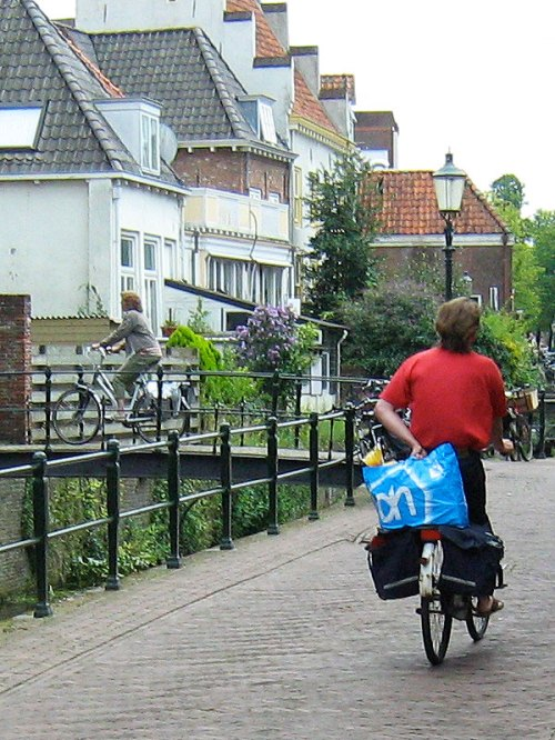 A person cycles home from the shops in Amersfoort, Netherlands. Both panniers are full and they are holding a large shopping bag on the rack behind them.