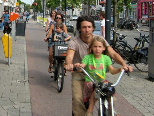 A family riding bikes on a cycle path in the Netherlands.