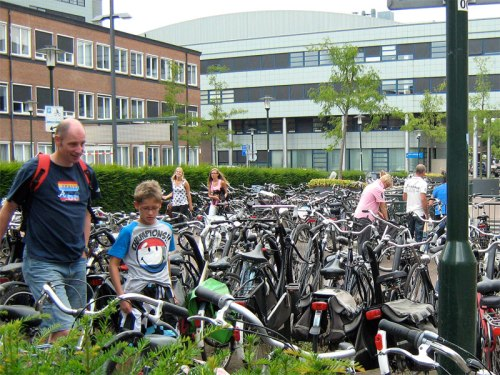 A bike parking lot outside a supermarket in the Netherlands. Hundreds of bikes can be seen with customers amongst them.
