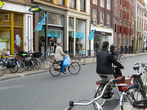 Cycles are parked ouside shops in Groningen, a woman is riding away with shopping bags hanging from her bike. A man waits with his Saint Bernard dog in the large front compartment of his 'bakfiets'.