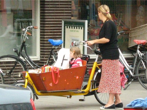 In the Netherlands, a mother cycles to the shops with her young daughter in the large container at the front of the bike.