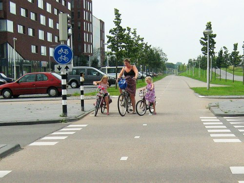 A mother and her two daughters set off at the traffic lights.