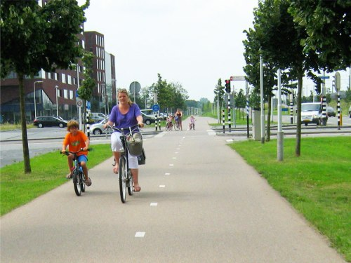 A woman and her son ride safely along a cycle path in the Netherlands.