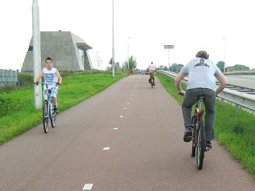 A boy rides down a hill on a wide cycle path in the Netherlands, safely protected from the busy road.