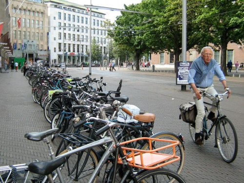 An older man rides his bike past hundreds of parked bikes in a city centre in the Netherlands
