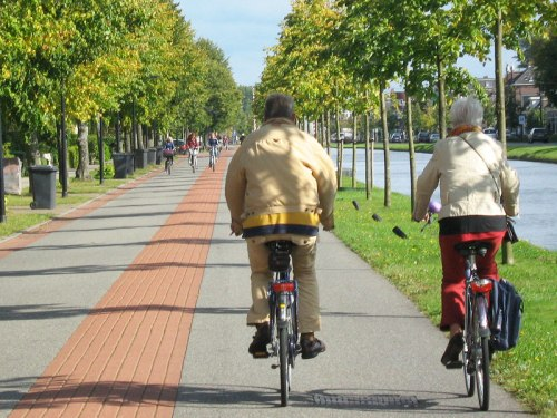 An older couple ride their bikes along a bicycle road in the Netherlands