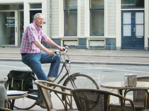 A late-middle-aged man calmly rides his bike past a cafe in the Netherlands