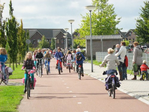 Groups of schoolchildren ride their bikes on a safe, wide cyclepath in the Netherlands.
