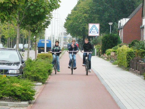Three boys ride on a Dutch cyclepath, protected from the traffic on the road.