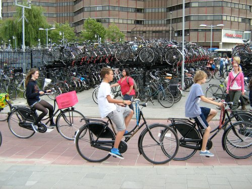 Three Dutch kids ride their bikes past one of the many bike parking areas in Utrecht.