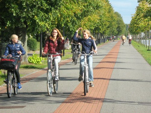 Three Dutch girls ride home on a 'bicycle road' alongside the canal in the Netherlands.