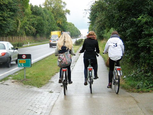 Three teenagers ride bikes on a rural cycle path in the Netherlands – up-hill!