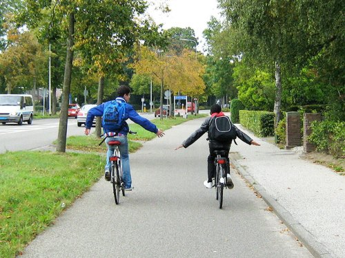 Two boys riding home from school, practising riding no-handed! They are safely on a cycle track away from the motor traffic.