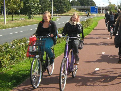 Two teenagers ride their bikes on a cyclepath in the Netherlands, protected from the main road.