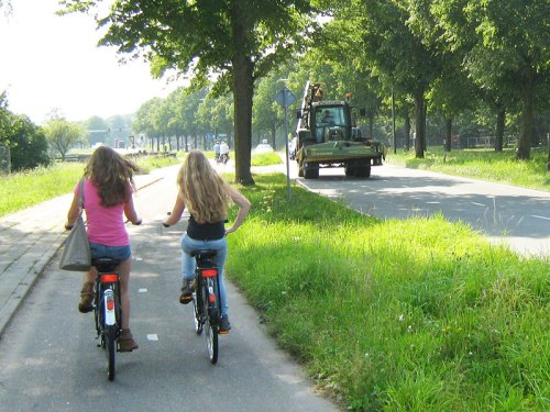 Two girls ride on a cycle path in Holland, beside a busy road with a tractor on it.