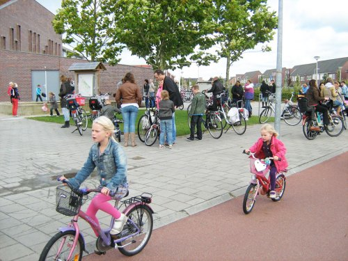 Two young girls ride bikes home from school in the Netherlands, safely on the cycle path, away from motor vehicles.