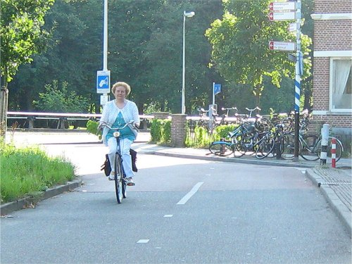 An older woman rides a bike on the safe cycle infrastructure in the Netherlands