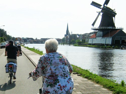 A grey-haired woman rides a bike alongside a canal and a windmill in the Netherlands