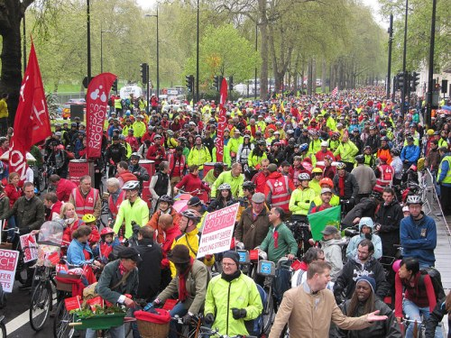 London Cycling Campaign's 2012 rally, called the Big Ride. Thousands of people on bikes are attending, but very many are wearing helmets, high-visibility clothing, and lycra.
