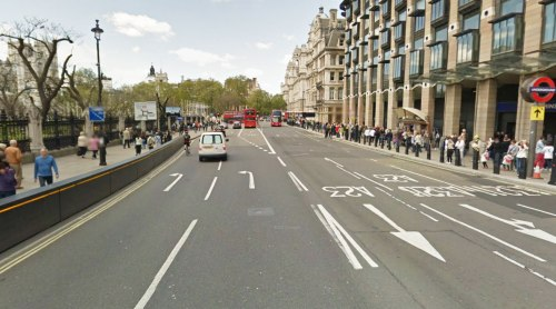 The end of Westminster Bridge beside Big Ben in London – masses of space given to motor vehicles, people crammed onto footpaths