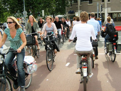 Rush hour in central Utrecht, Netherlands. Many people of all ages riding bikes in their normal clothes, without the safety equipment deemed necessary in the UK.