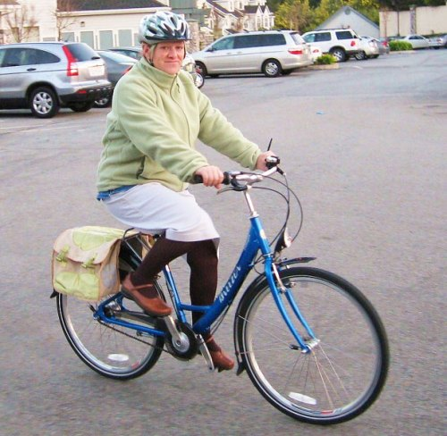 A middle-aged woman riding a bike.