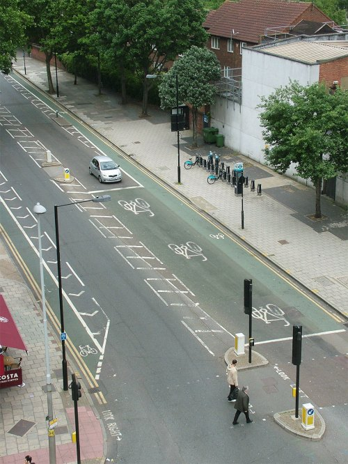 An altered photograph showing a junction with an extremely long (20m or so) ASZ, to demonstrate why ASLs aren't compatible with large numbers of people cycling.