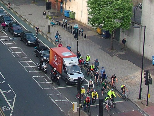 A birds' eye photo of a UK road junction with an ASL. All vehicles are positioned perfectly, no motor vehicles have entered the ASZ. But the ASZ can only hold around ten bikes, and there are twenty in shot, overflowing up the left-hand side of motor vehicles waiting.