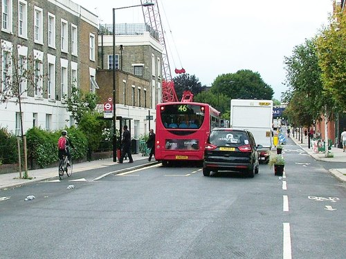 A photograph of the second bus stop on Royal College Street. There's enough space for a large van to pass the stopped bus, while a bike user has to stop while passengers board and alight the bus.