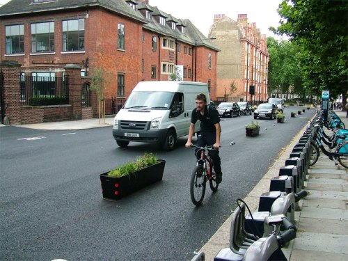 A man riding a bike along the Royal College Street cycle lane. He is well away from the kerb.