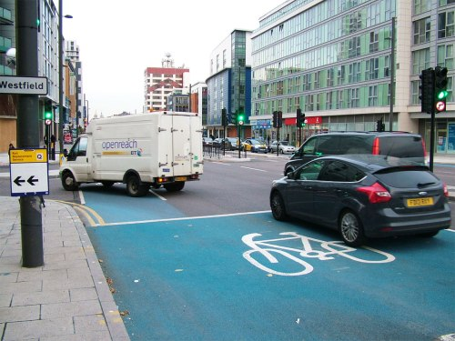 A van turns left while cyclists are green to go straight on, on CS2 at Stratford
