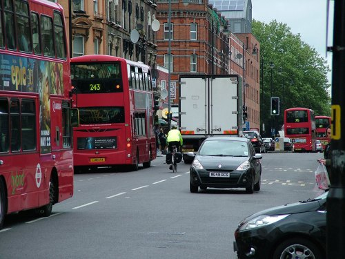 Kingsland High Street in Hackney, London. A bus is stopped, and a lorry is overtaking it. A cyclist dressed in high-visibility clothing follows the lorry, and a bus follows the cyclist.