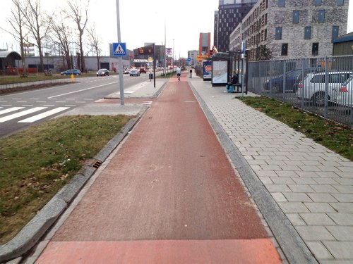 Cycleway on Sontweg in Groningen. Made of red asphalt. Cycleway passes a bus stop, which is on a raised platform by the road.